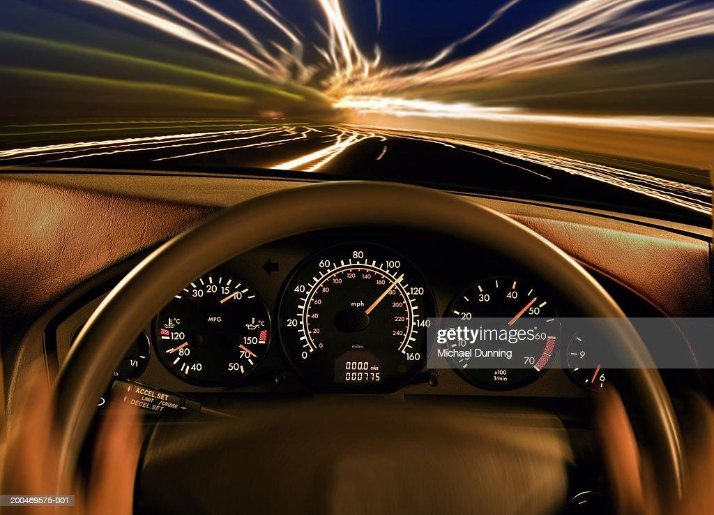 Dashboard of car, close-up, dusk, (blurred motion)