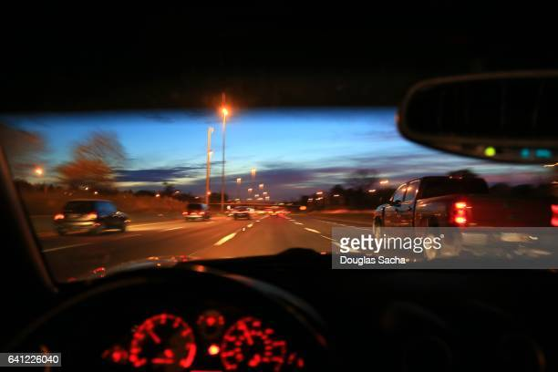 Dashboard view of a car moving on a highway in the evening hour