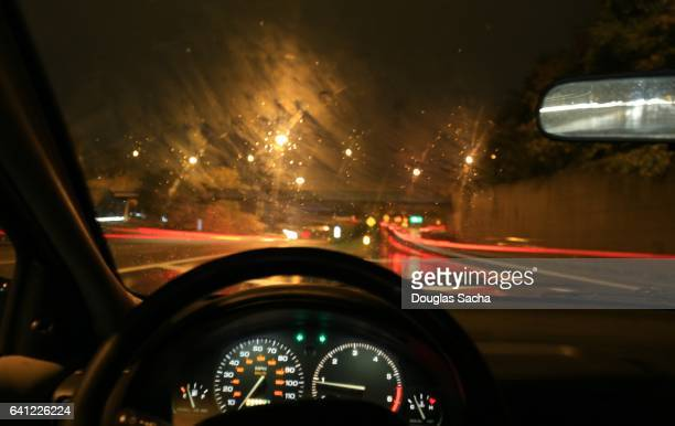 Dashboard view of a moving car on a rainy night