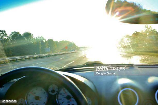 Dashboard view of a moving car viewing the bright sunlight