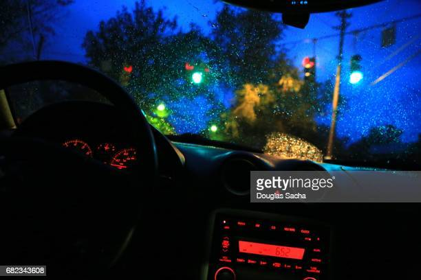 Dashboard view of a roving vehicle on a rainy night
