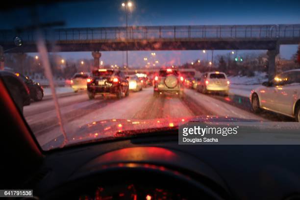 Dashboard view of a slow moving car on a snowy night