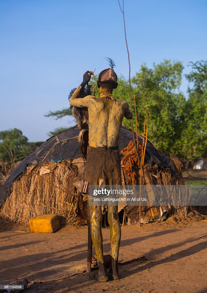 Dassanech man dressing with a leopard skin for dimi ceremony to celebrate circumcision of the teenagers omo valley omorate Ethiopia on March 21 2016...