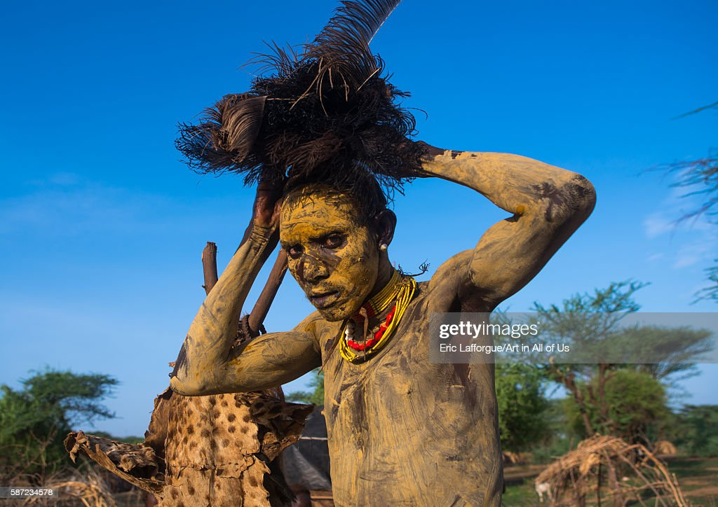 Dassanech man dressing with an ostrich feathers headwear for dimi ceremony to celebrate circumcision of the teenagers omo valley omorate Ethiopia on...