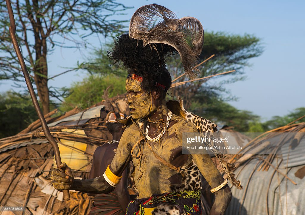 Dassanech man with leopard skin and ostrich feathers headwear during dimi ceremony to celebrate circumcision of teenagers omo valley omorate Ethiopia...