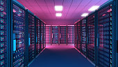 Data center server room at night illuminated by blue and purple lights with rows of black cabinets. Dark scene with dim illumination. Aisle surrounded by black cabinets with glass doors protecting ser