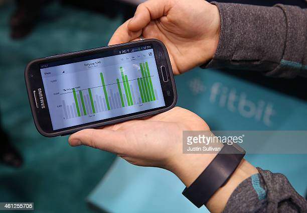 Data collected from the Fitbit Force is displayed on a smartphone in the Fitbit booth at the 2014 International CES at the Las Vegas Convention...