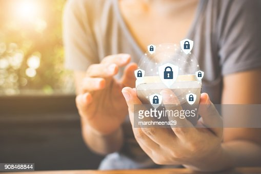 Data protection and security important information in your mobile phone, Woman hand using smartphone and icon key on shield : Stock Photo