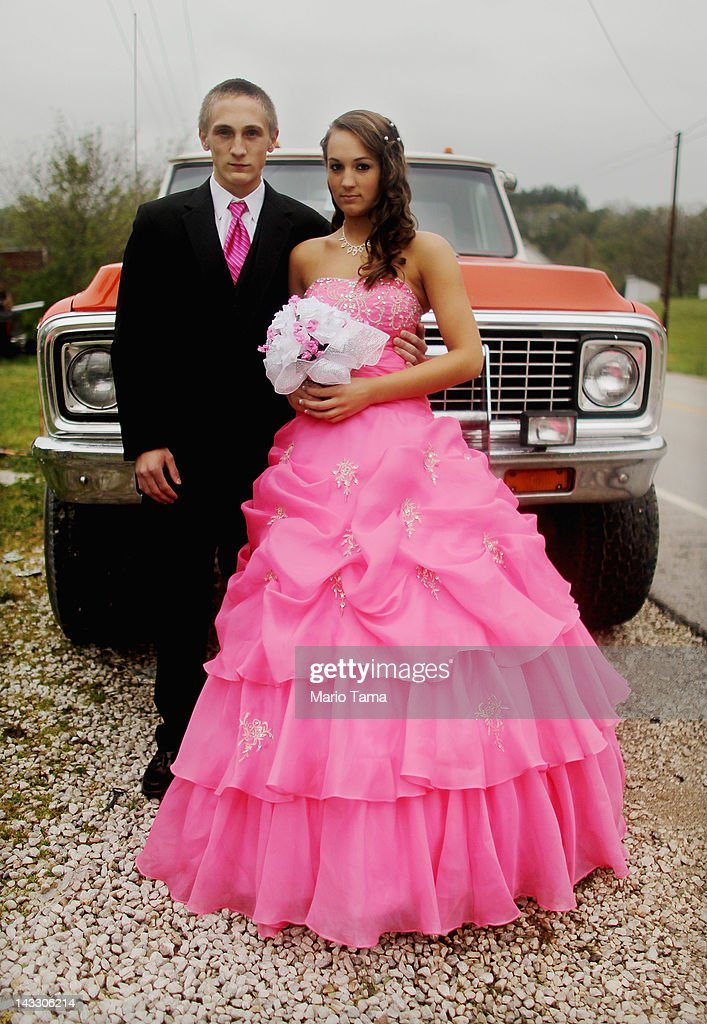 Dates Coty Shouse (L) and Destiny Duff pose in front of the vehicle they will take to prom while preparing for the Owsley County High School prom on April 21, 2012 in Booneville, Kentucky. Daniel Boone once camped in the Appalachian mountain hamlet of Owsley County which remains mostly populated by descendants of settlers to this day. The 2010 U.S. Census listed Owsley County as having the lowest median household income in the country outside of Puerto Rico, with 41.5% of residents living below the poverty line. Familial and community bonds run deep, with a populace that shares a collective historical and cultural legacy uncommon in most parts of the country. However, the community of around 5,000 struggles with a lack of jobs due to the decline in coal, tobacco and lumber industries along with health issues including drug addiction without effective treatment.