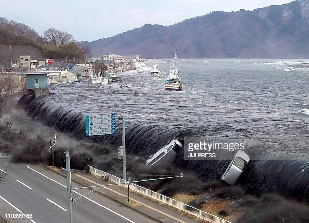 DATEThis picture taken by a Miyako City official on March 11 2011 and released on March 18 2011 shows a tsunami breeching an embankment and flowing...