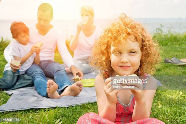 Dating with children, reconstituted family picnicking on riverside.