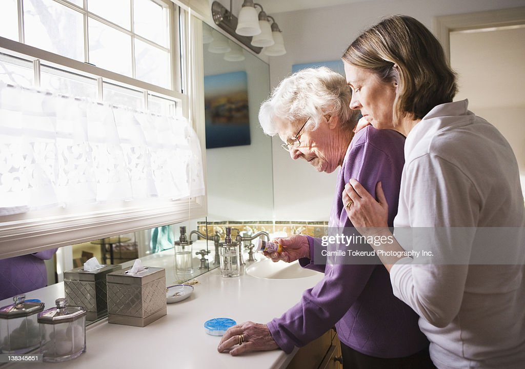Daughter and Elderly mother checking medicine