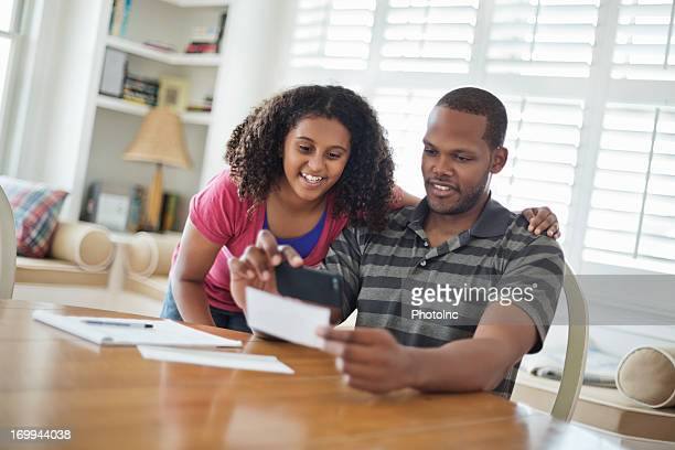 Daughter And Father Paying Bill Using Mobile Phone