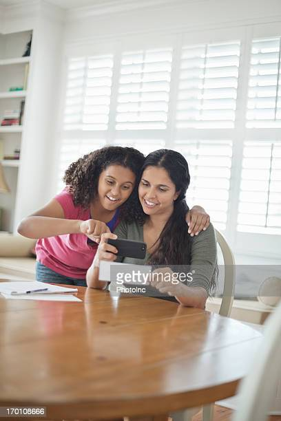 Daughter And Mother Depositing Bank Slip Through Phone