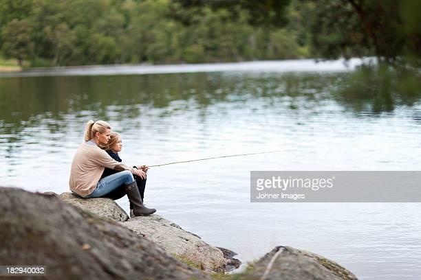 Daughter and mother fishing at lake