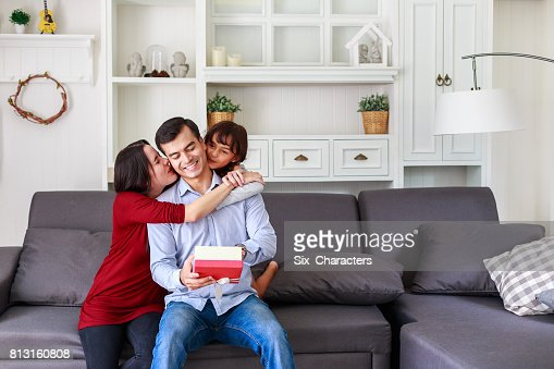 Daughter and mother surprising father with gift at home in the living room, Mother with kids celebrating father's day : Stock Photo