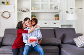 Daughter and mother surprising father with gift at home in the living room, Mother with kids celebrating father's day