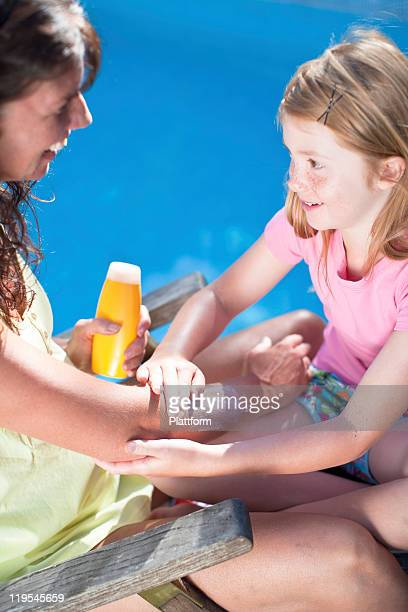 Daughter applying suntan lotion on her mothers arm