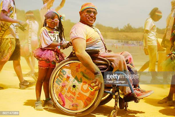 Daughter assisting father in wheel chair/ ColorRun