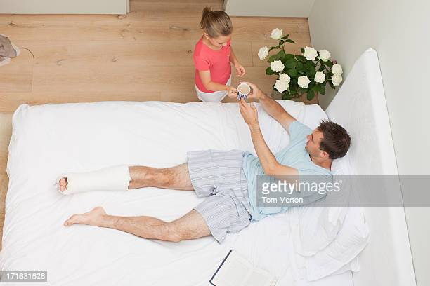 Daughter bringing coffee to father with broken leg