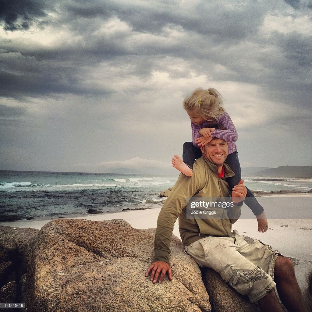 Daughter climbing on fathers shoulders at beach : Stock Photo