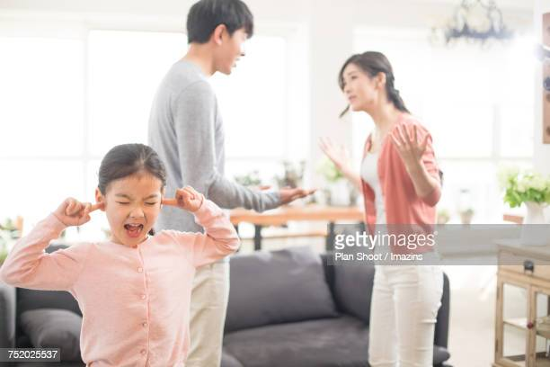 Daughter closing her ears while couple is fighting