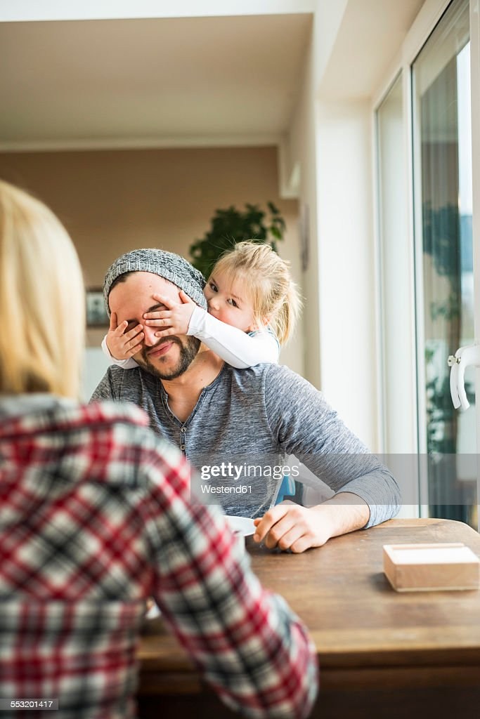 Daughter covering fathers eyes