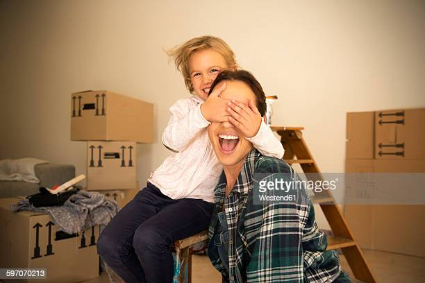 Daughter covering mothers eyes with cardboard boxes in background