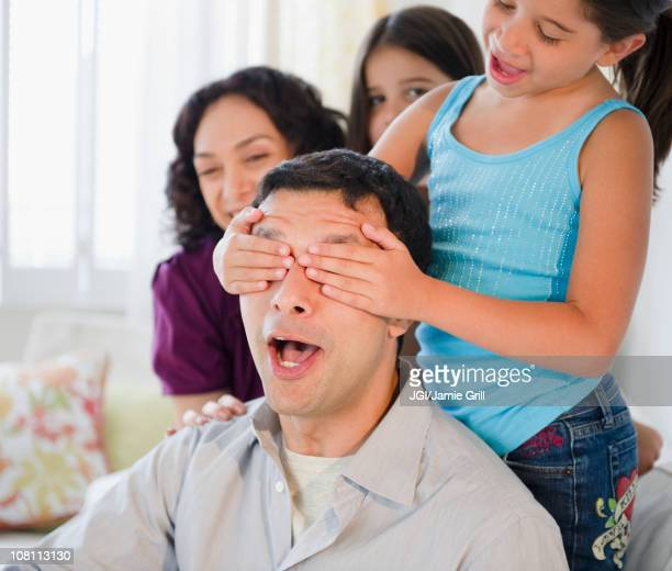 Daughter covering surprised father's eyes