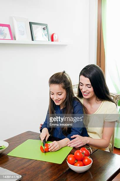 daughter cutting tomatoes with mum