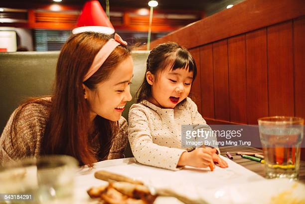 Daughter drawing with mom in restaurant