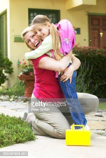 Daughter (7-9) dressed for school hugging mother
