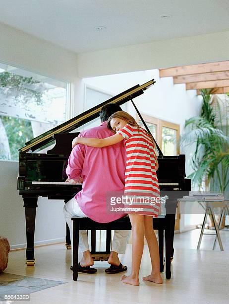 Daughter embracing father by piano