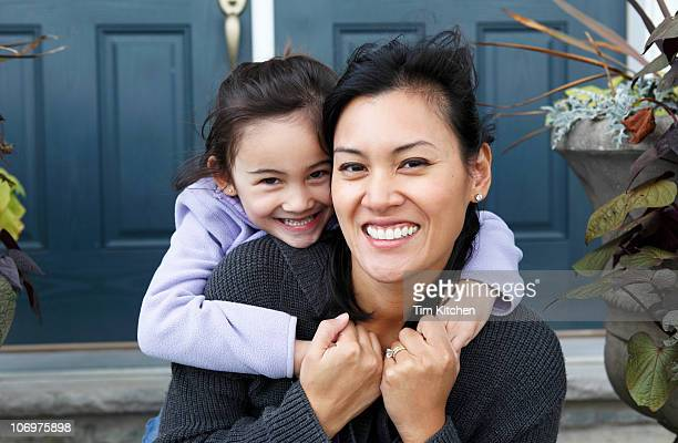 Daughter embracing mother on front doorstep