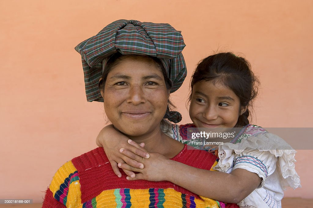 Daughter (6-8) embracing mother, smiling, portrait of mother : Stock Photo
