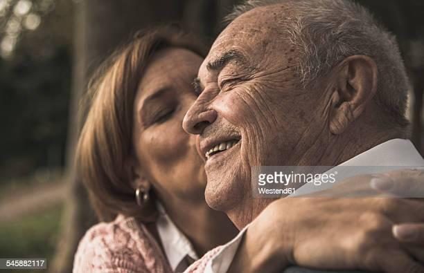 Daughter embracing senior man outdoors