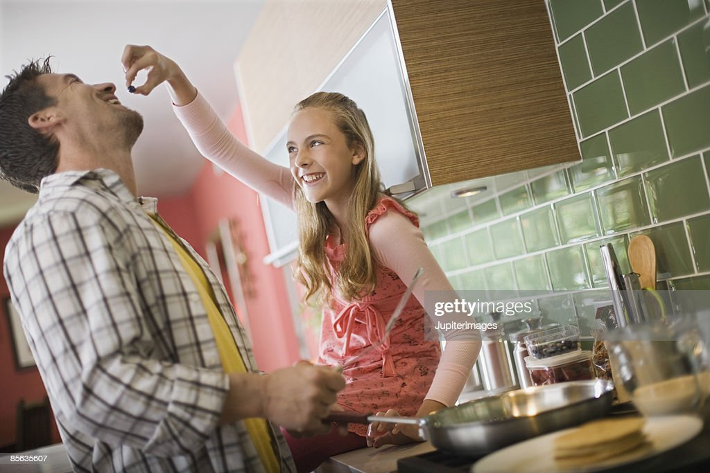 Daughter feeding blueberry to father : Stock Photo