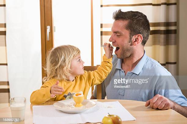 Daughter feeding boiled egg to father