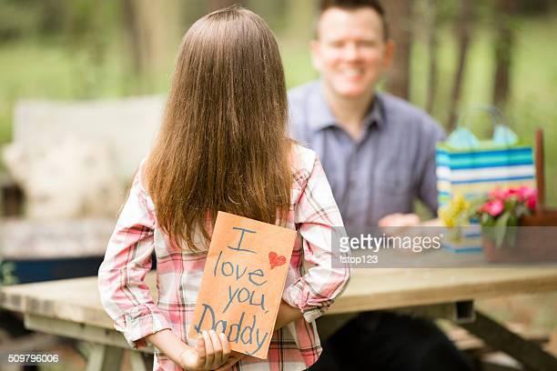 Vater mit Tochter bietet handgefertigte Vatertag-Karte.   Im Freien.   Kinder, Eltern.
