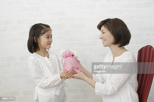 Daughter giving gift to mother
