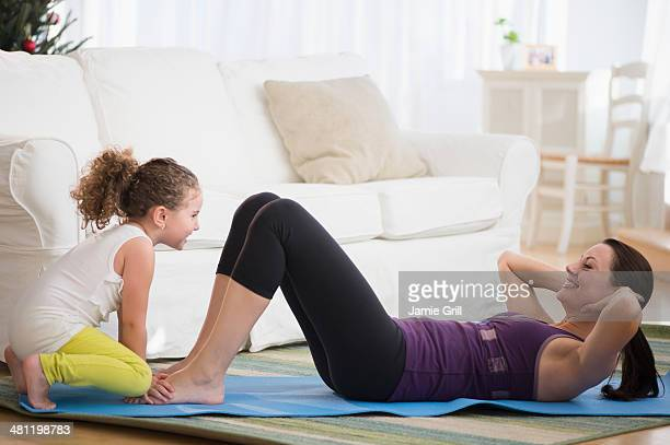 Daughter helping mother exercise