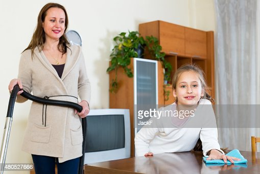 Daughter helps mother with cleaning : Stock Photo