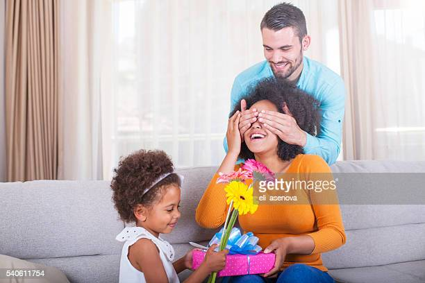 Daughter holding gift and flowers, father covering mothers eyes