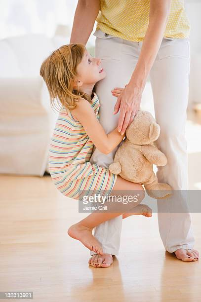Daughter holding onto her mother's leg