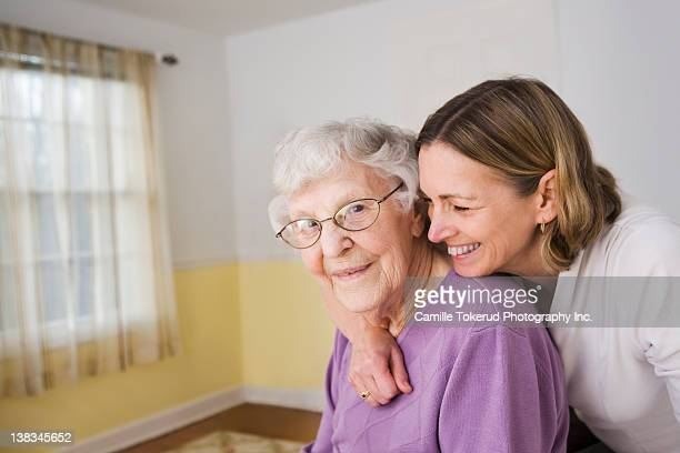 Daughter hugging Elderly mother