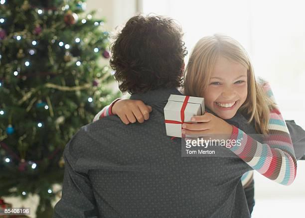 Fille embrassant père tenant un cadeau de Noël