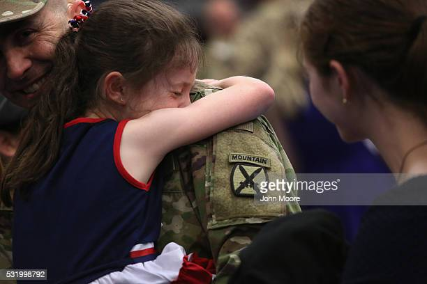 A daughter hugs her father after he and fellow soldiers returned from Iraq on May 17 2016 at Fort Drum New York More than 1000 members of the 10th...
