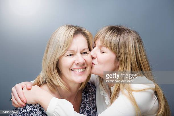 Daughter kisses mother on cheek.