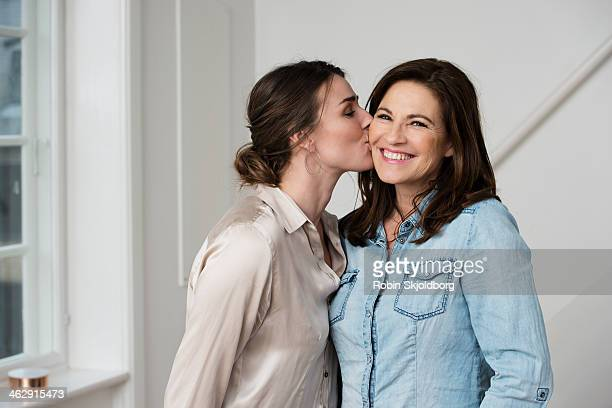 Daughter kissing mature mother on cheek