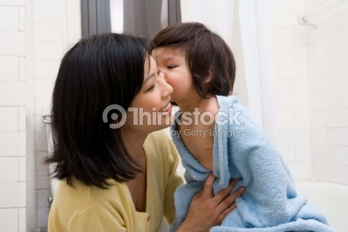 Daughter Kissing Mother In Bathroom Stock Photo